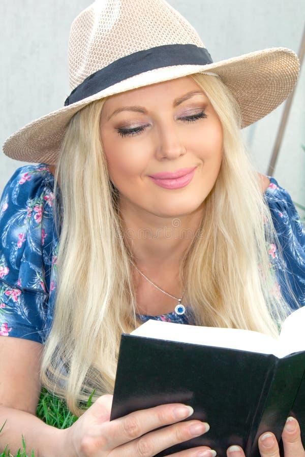 画象特写镜头 帽子的美丽的白肤金发的年轻女人在草说谎并且读书 库存照片