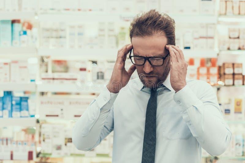 画象男性顾客有头疼在药房 免版税库存图片
