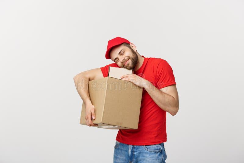 画象盖帽的送货人有作为拿着两个空的纸板箱的传讯者或经销商的红色T恤杉工作的 ?? 免版税库存图片