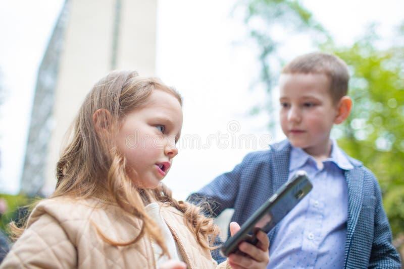 画象结合孩子、男孩和一个女孩有室外的电话的 小成人推测关系 不快乐地 免版税库存照片