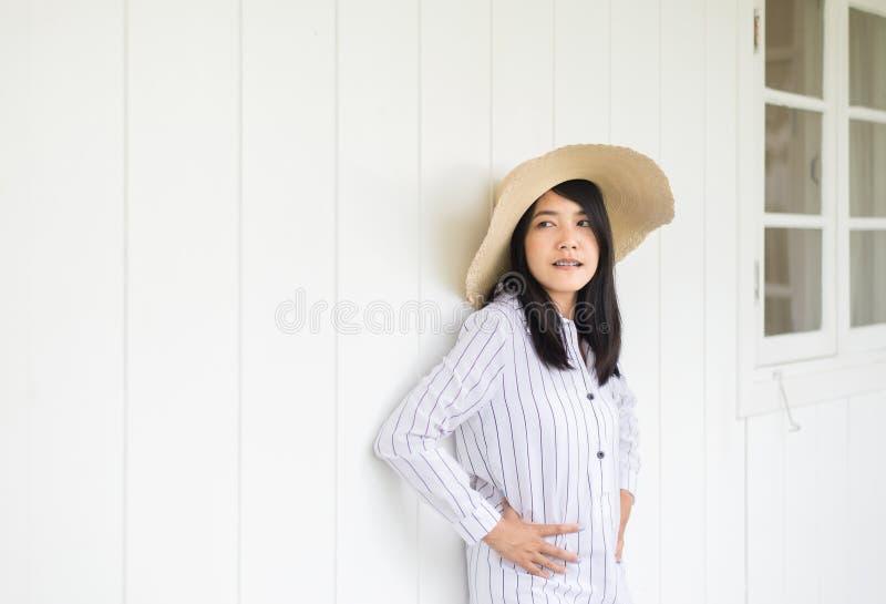 画象美丽的亚裔妇女佩带的帽子和在家站立,正面认为,好态度 库存图片