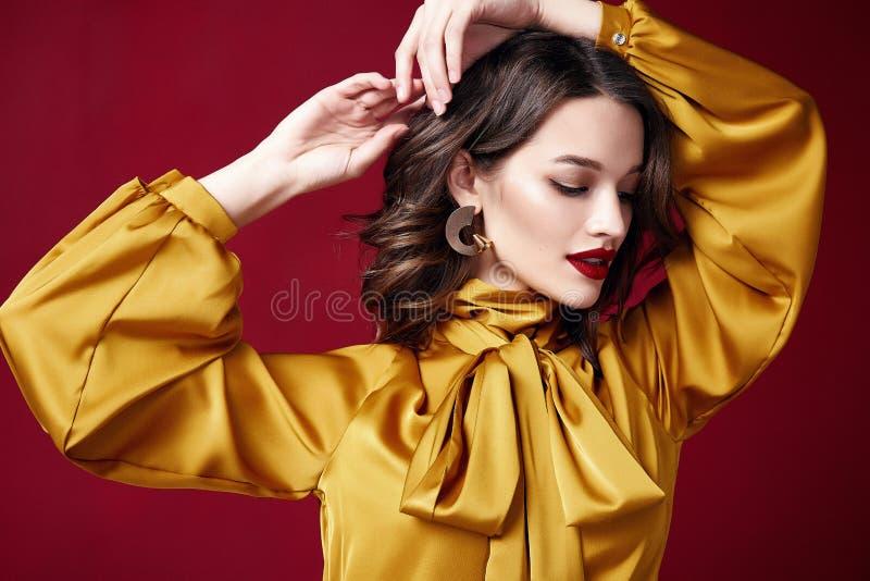 画象美丽的俏丽的妇女红色口红首饰耳环深色的头发化妆构成时尚衣裳发廊 库存照片