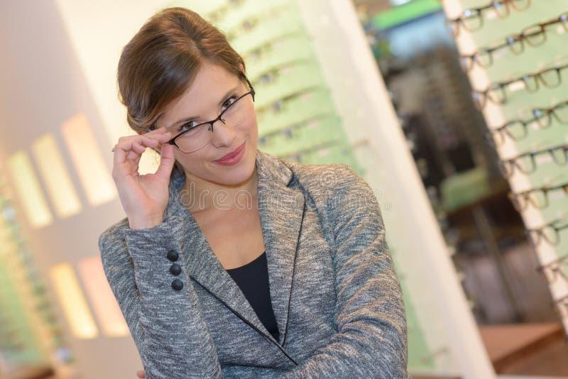 画象美丽的妇女佩带的玻璃在眼镜师商店 免版税库存照片