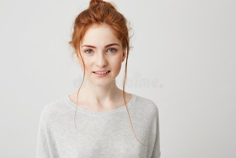 画象美丽的嫩姜女孩微笑的摆在看在白色背景的照相机 免版税库存图片