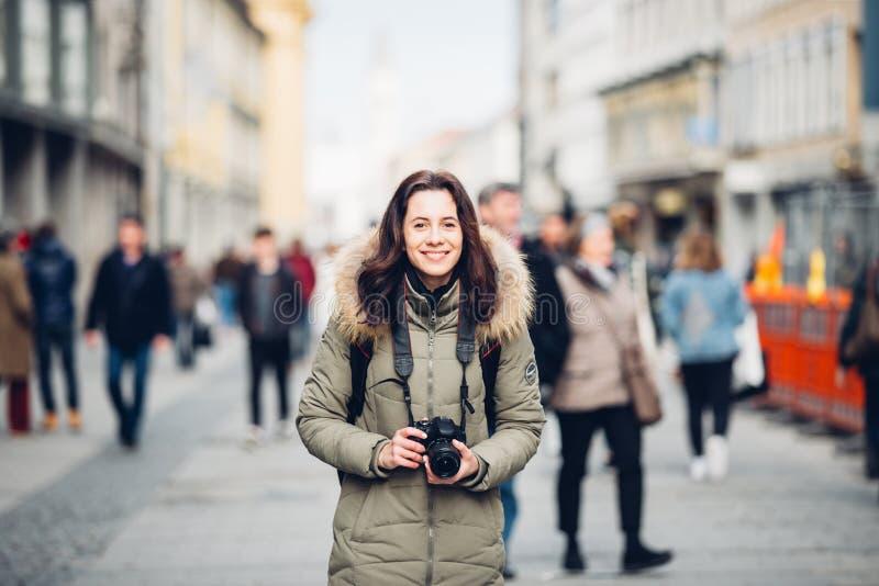 画象美丽的年轻旅游妇女在人人群的背景中站立在一条中央街道上的在慕尼黑在w的德国 库存图片