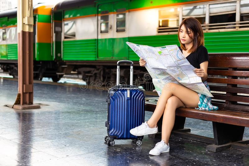 画象美丽的旅客妇女 俏丽的女孩注视着一张地图火车站 美女计划去游人 免版税库存图片
