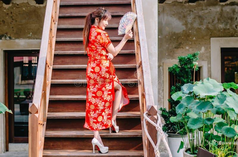 画象美好的年轻女人微笑穿举行在台阶的cheongsam深红礼服一个爱好者身分在性感的姿势 免版税库存图片