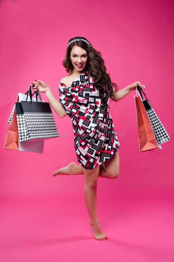 画象跳跃全长愉快的妇女在手上拿着纸购物带来和,摆在照相机 色的佩带 免版税库存图片