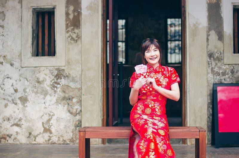 画象迷人的美丽的亚裔女服cheongsam装饰开放与金钱的红色信封,在农历新年 免版税库存图片