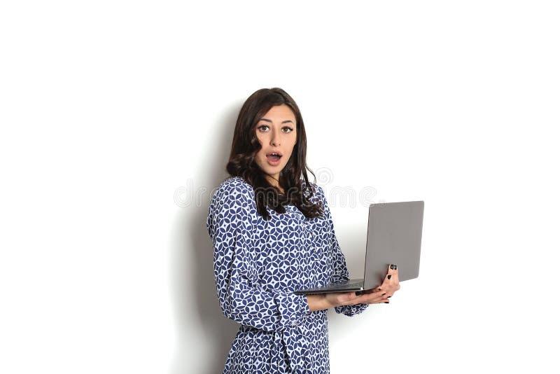 画象,微笑的确信的俏丽的妇女长的袖子礼服,拿着灰色膝上型计算机设备和键入,当站立反对坚实whi时 免版税库存图片