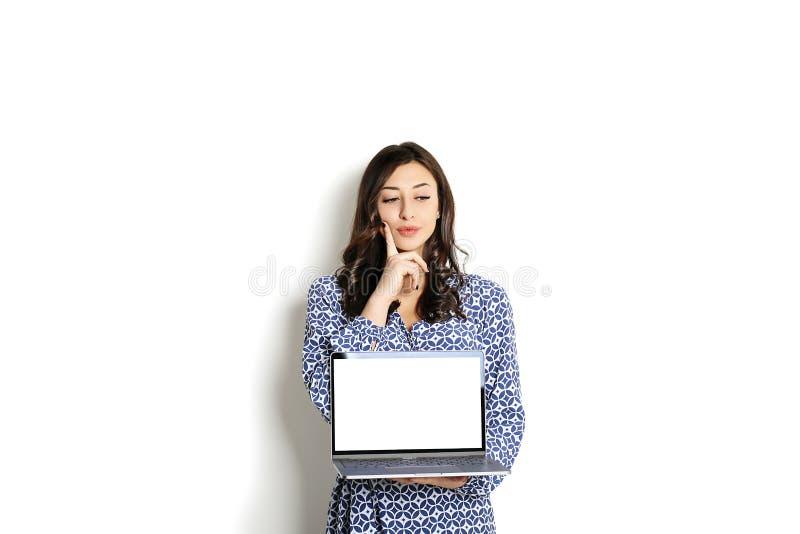 画象,微笑的确信的俏丽的妇女长的袖子礼服,拿着灰色膝上型计算机设备和键入,当站立反对坚实whi时 库存照片