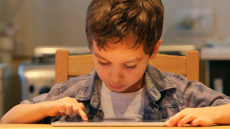 画象:逗人喜爱的小孩在家使用一台片剂个人计算机在桌 免版税库存图片