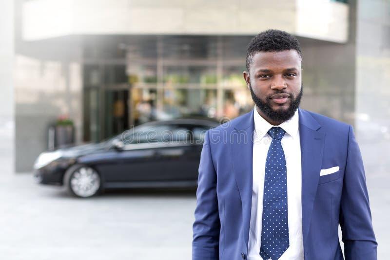 留下他的黑汽车的年轻非洲商人在办公楼 免版税库存照片