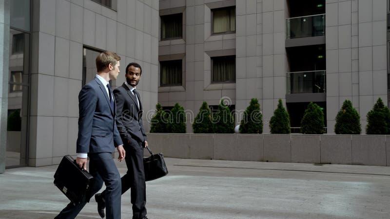 留下办公楼的商务伙伴谈论起始,重要会议 免版税库存图片