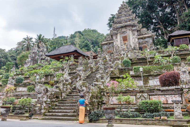 留下奉献物的巴厘语妇女在Pura Kehen,巴厘语印度寺庙在Bangli摄政,巴厘岛,印度尼西亚 图库摄影