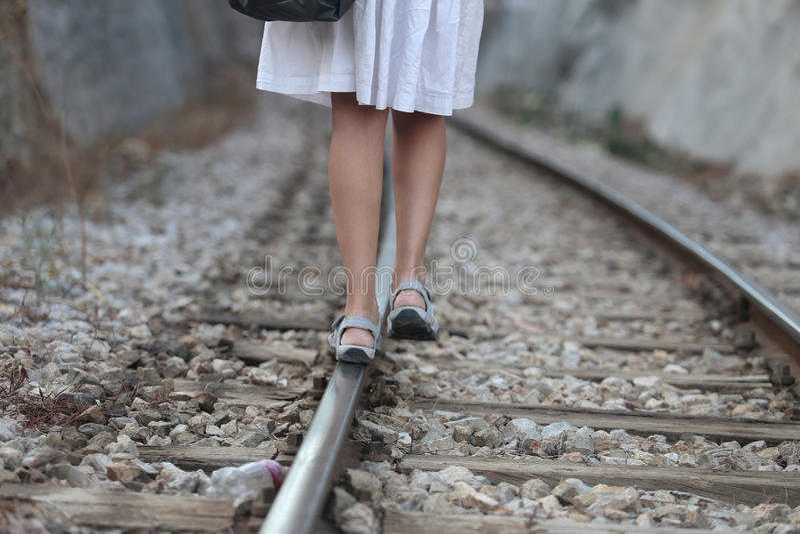 留下走在路轨道路的女孩 免版税库存照片