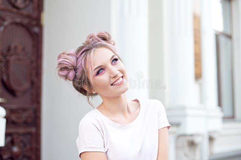 留着她的在小圆面包欣喜的愉快的快乐的年轻女人桃红色头发在正面新闻或生日礼物,看 免版税库存照片