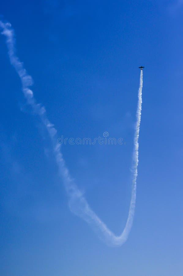 留给烟雾的痕迹的小飞机蓝天在背景 免版税图库摄影