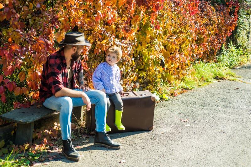 留胡子的父子在树林里散步后在长椅上放松 家庭休闲 育儿 为人父母 秋常春藤 库存照片