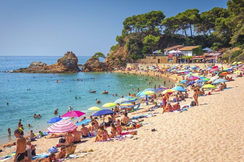 略雷特德马尔,肋前缘Brava,西班牙-威严22日2018年:与游人的热带海滩 晒日光浴在沙滩Platja de Fenals 免版税库存图片