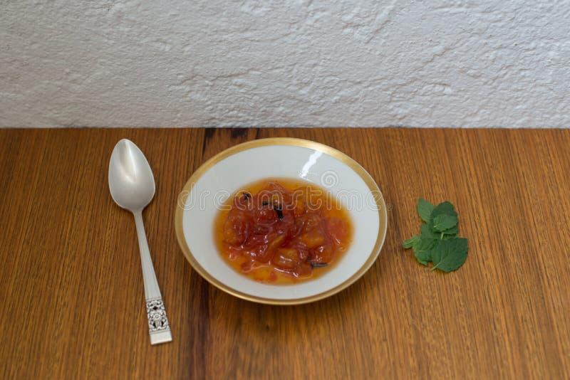 番木瓜点心印度丁香蓬蒿叶子在与生来有福的中国瓷盘服务 免版税库存图片
