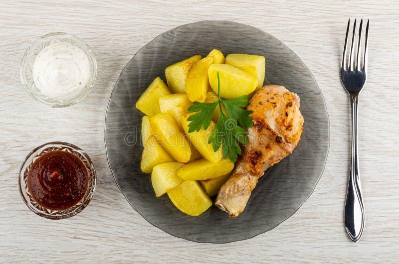 番茄酱和蛋黄酱,烤鸡腿用在灰色板材,在木桌上的叉子的油煎的土豆 r 免版税库存照片