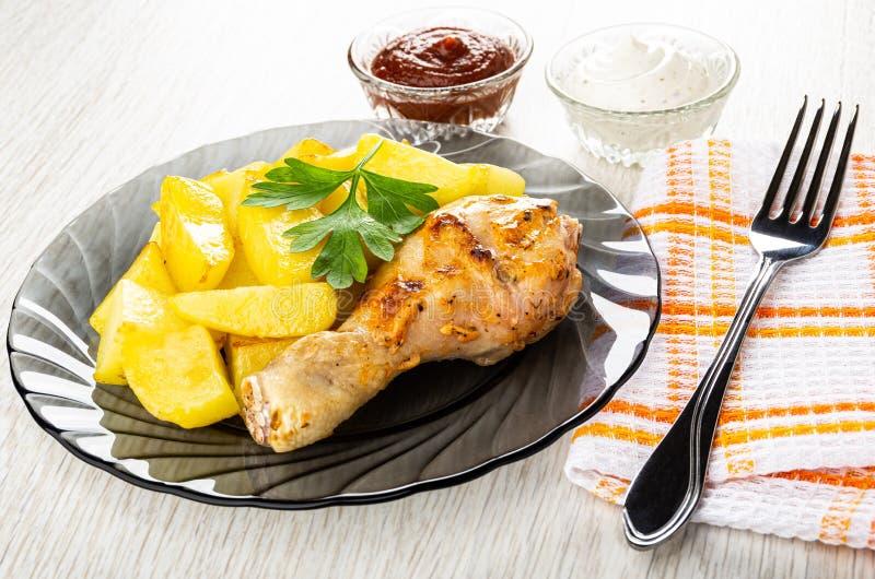 番茄酱和蛋黄酱,烤鸡腿用在灰色板材,在餐巾的叉子的油煎的土豆在木桌上 库存照片