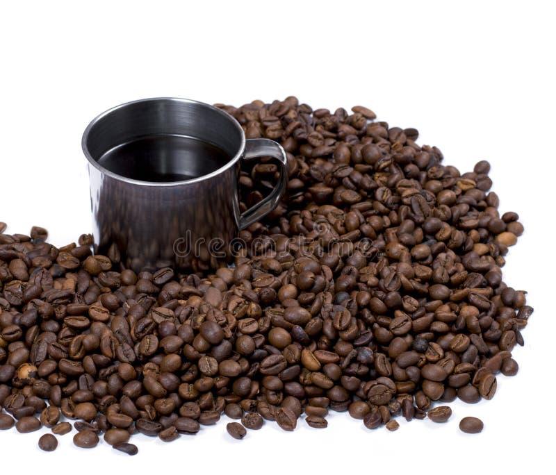 疏散咖啡粒和钢杯子 库存照片