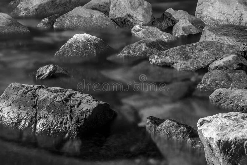 疏散在海水与可看见的纹理浸没的岩石和石头 单色,黑白构成 库存照片