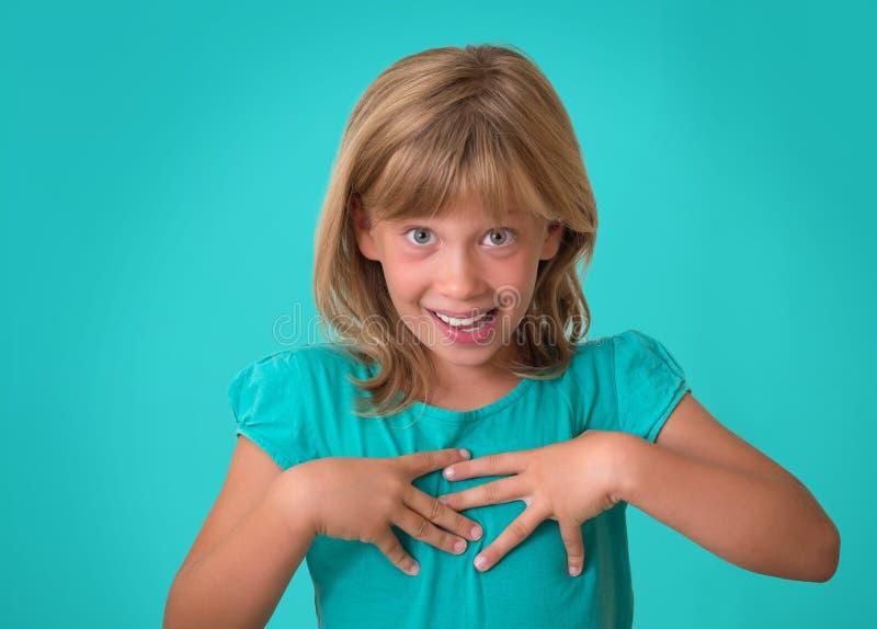 疑惑地指向她自己的女孩与谁,我?表示 得到意想不到的关注的惊奇的,小女孩从pe 免版税库存图片