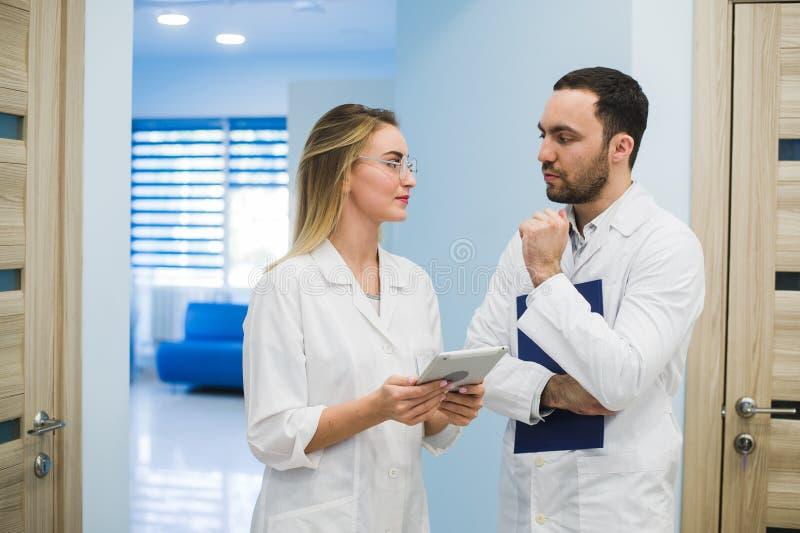 医疗人员有论述在现代医院走廊 免版税库存照片