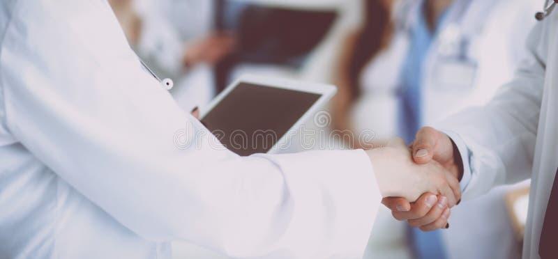 年轻医疗人握手在办公室 库存照片