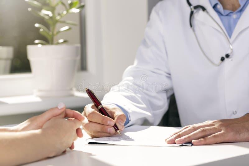 医疗会诊-坐由桌的医生和患者 免版税库存图片