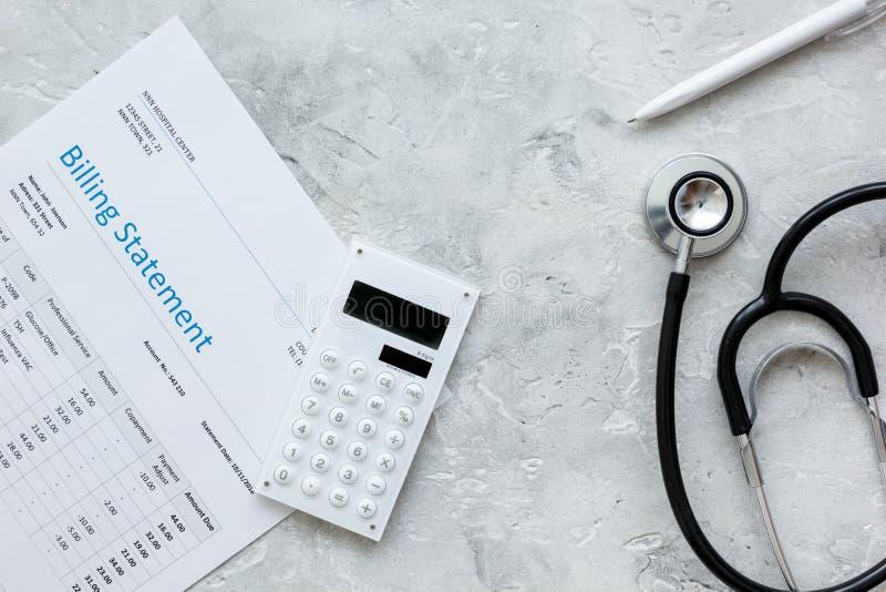 医疗保健与医生的听诊器和笔的布告声明在石背景顶视图 免版税库存图片