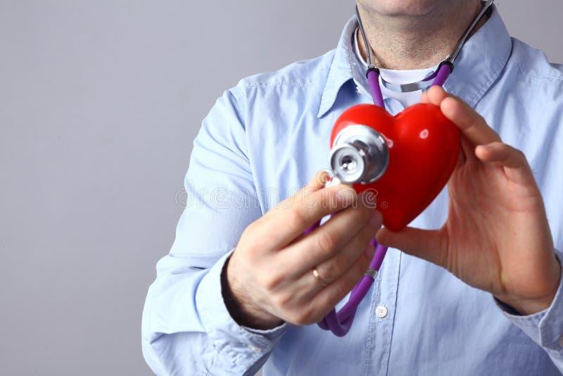 医疗保健和医学概念-接近男性医生递拿着红色心脏和医疗听诊器 库存照片