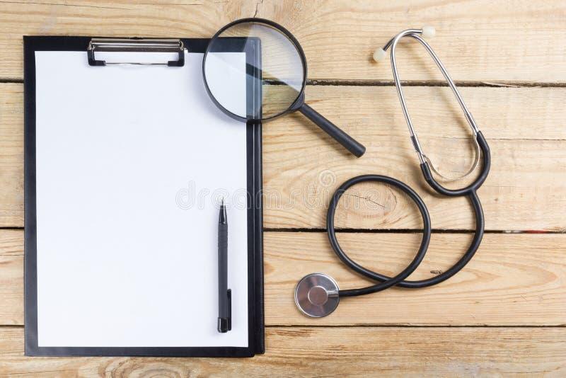 医疗剪贴板和听诊器,放大镜,在木书桌背景的黑笔 顶视图 医生的工作场所 免版税库存图片
