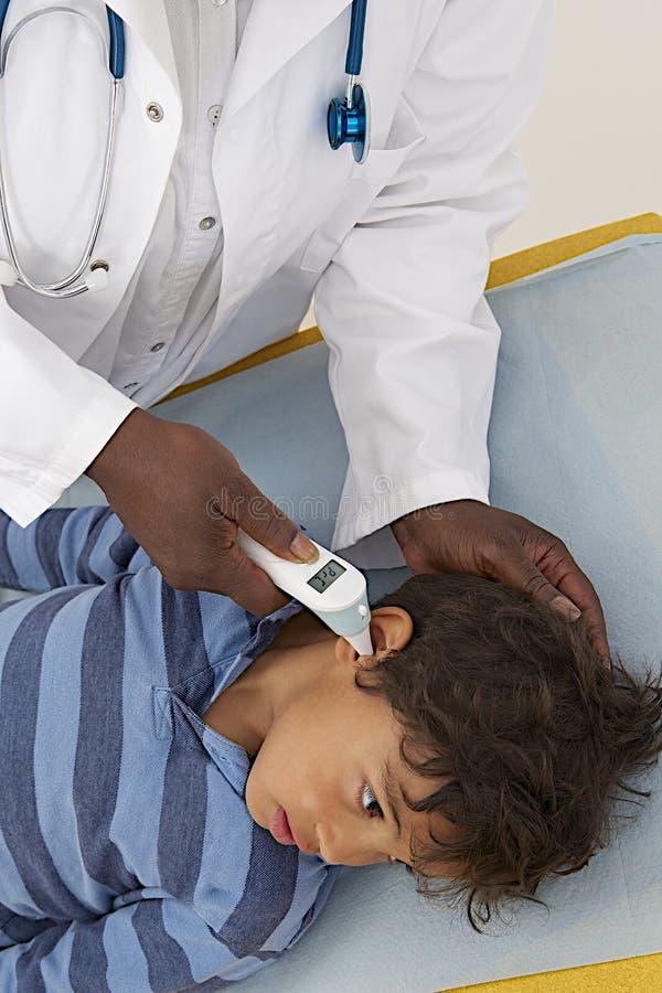医疗参观-年轻男孩温度测量 免版税库存图片