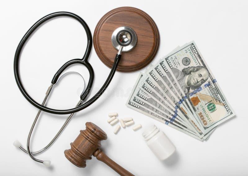 医疗听诊器、药片、法官锤子和金钱在白色后面 免版税库存照片