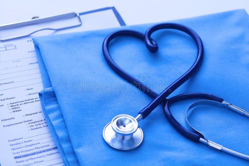 医疗听诊器在说谎在耐心病史名单和蓝色医生制服特写镜头的心脏形状扭转了 库存照片