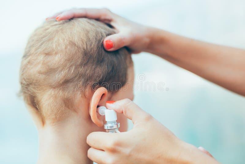 治疗小男孩耳朵传染的母亲 库存照片