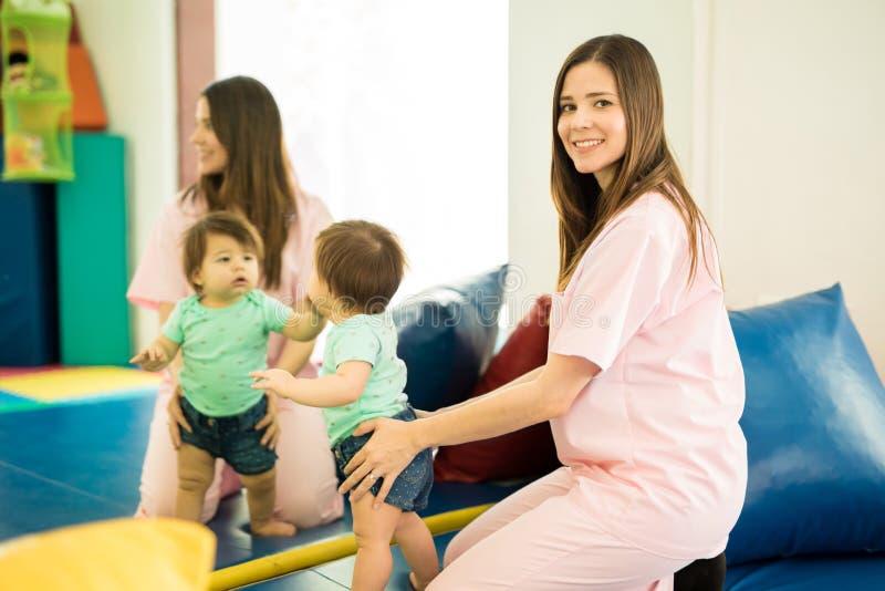 治疗师和婴孩在镜子前面 免版税库存图片