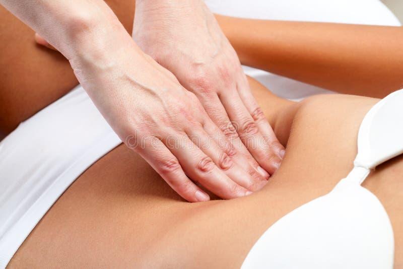 治疗师手按在女性腹部 库存照片