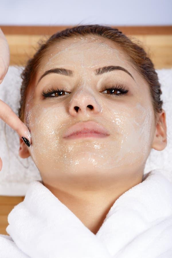 治疗师的手应用奶油于妇女的面孔 残破的关心概念对分重点被缝的冲程二妇女 库存图片