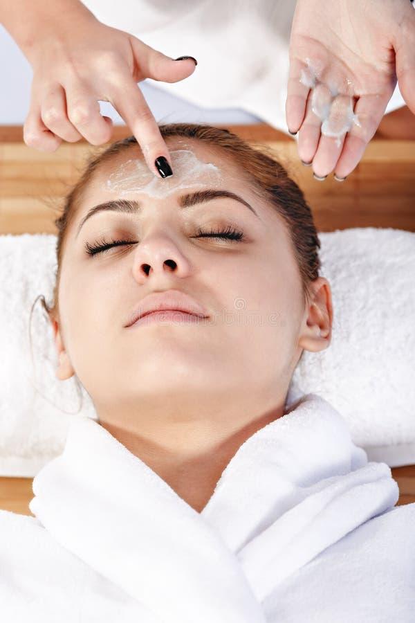 治疗师的手应用奶油于妇女的面孔 残破的关心概念对分重点被缝的冲程二妇女 免版税库存图片
