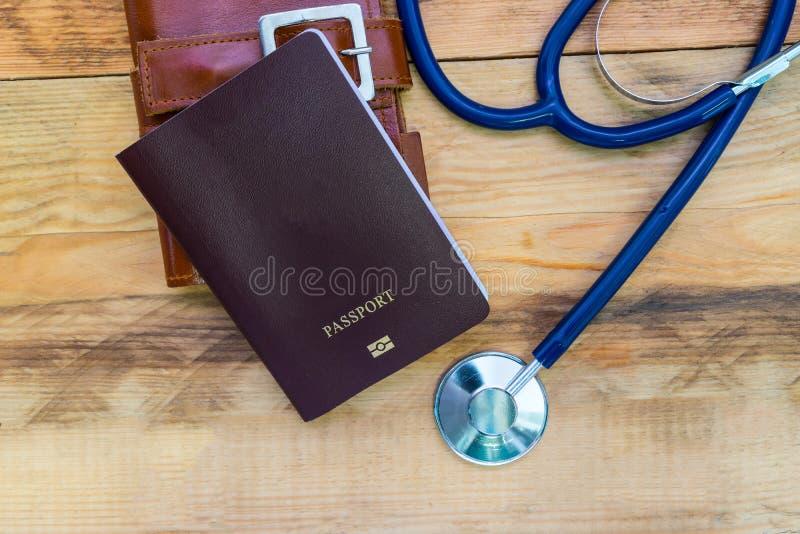 医疗旅游业概念 有护照的听诊器在木 图库摄影