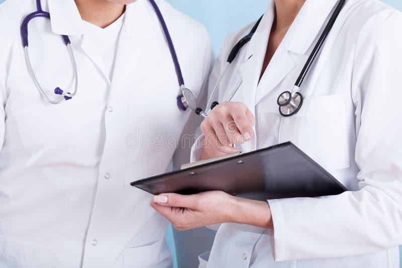 医疗白色围裙的医生与听诊器和剪贴板 免版税库存图片