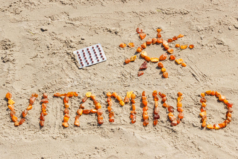 医疗药片、题字太阳维生素D和形状在沙子的在海滩,夏时和健康生活方式 库存图片
