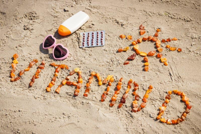 医疗药片、题字维生素D和辅助部件晒日光浴的在海滩,维生素D缺乏的预防 免版税库存图片