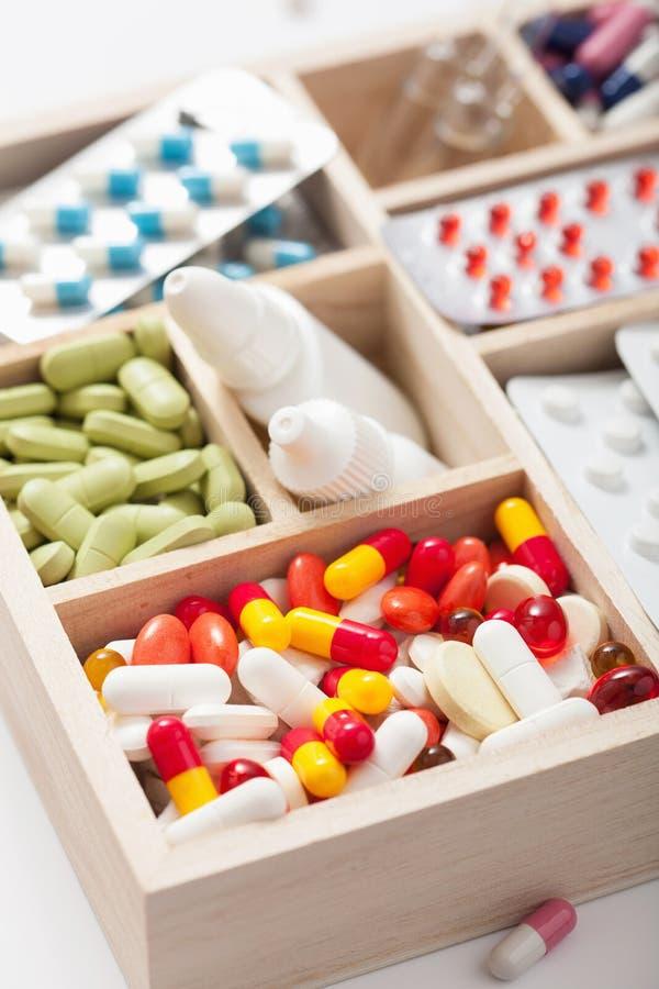 医疗药片和一次用量的针剂在木箱 库存图片