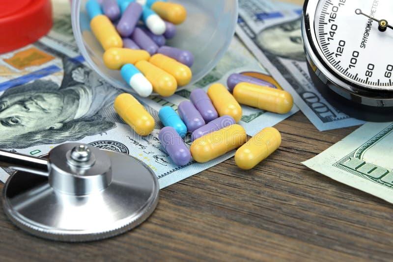 医疗设备、药片和胶囊在金钱在木表上 免版税图库摄影